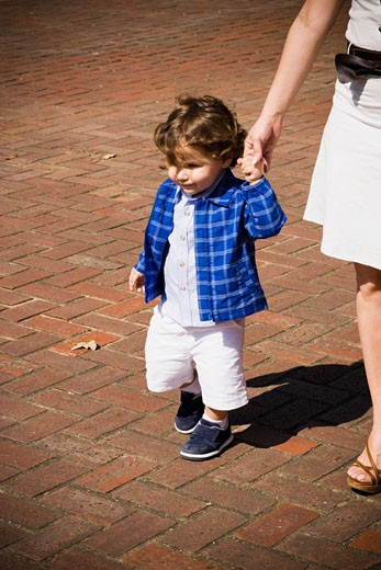 Baby boy holding his mother's finger and walking : Stock Photo