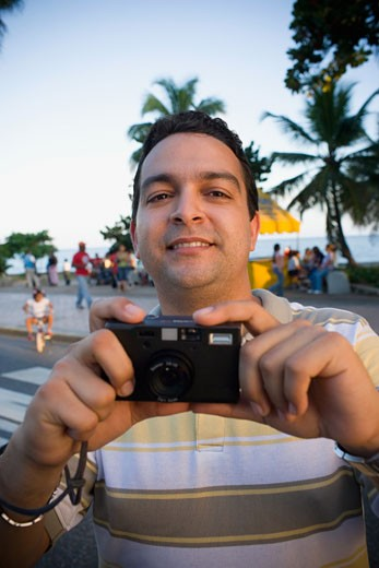 Mid adult man holding a camera : Stock Photo