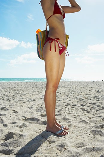 Stock Photo: 1757R-4723 Young woman strikes a pose on beach