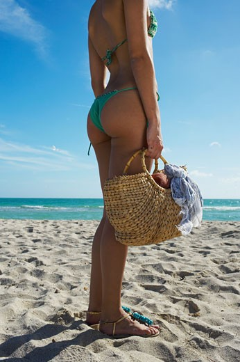 Young woman standing on beach with beach bag : Stock Photo