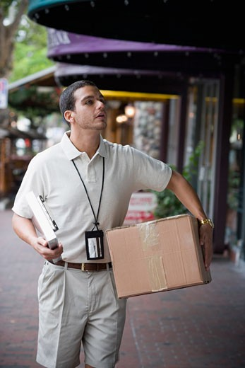 Delivery man carrying large box : Stock Photo