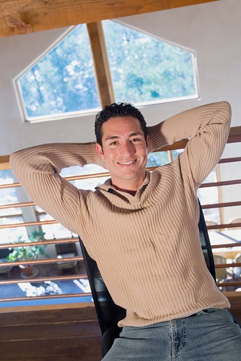 Stock Photo: 1757R-5418 Portrait of a mid adult man smiling with his hands behind his head
