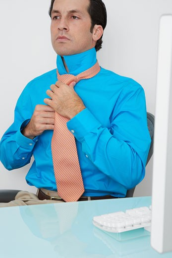 Businessman knotting his tie in an office : Stock Photo
