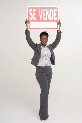 Stock Photo: 1757R-7083 Real Estate agent holding a For Sale (Se Vende) sign
