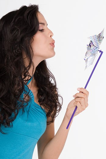 Stock Photo: 1757R-7350 Close-up of a teenage girl blowing a pinwheel