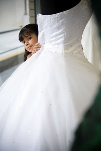 Stock Photo: 1757R-7437 Young girl looks peeks out from behind white gown
