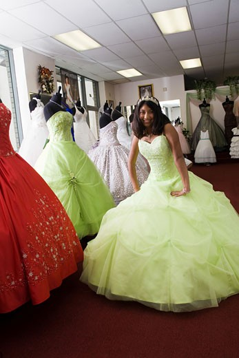 Teenage girl dances in party dress store : Stock Photo