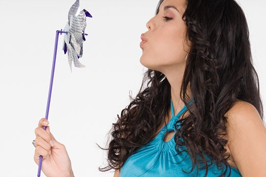 Stock Photo: 1757R-7641 Close-up of a teenage girl blowing a pinwheel