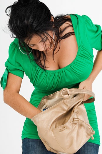 Close-up of a young woman searching in her bag : Stock Photo