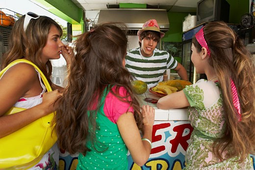 Three teenage girls talking with a bartender in a juice bar : Stock Photo