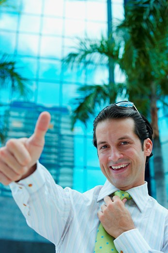 Stock Photo: 1757R-7992 Portrait of a businessman making a thumbs up sign and smiling