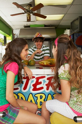 Two teenage girls talking with a bartender in a juice bar : Stock Photo