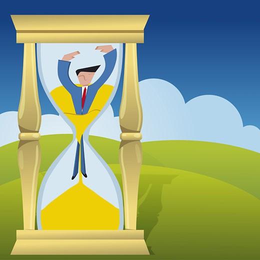 Businessman inside an hourglass : Stock Photo