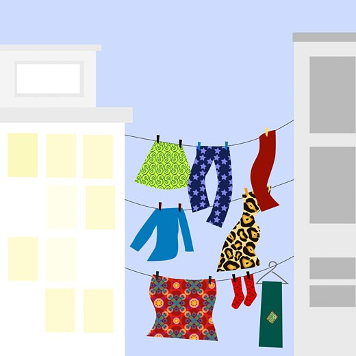 Clothes hanging on clotheslines between two buildings : Stock Photo