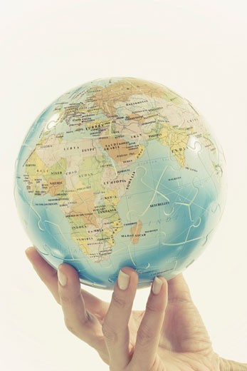 Close-up of a woman's hand holding a globe : Stock Photo