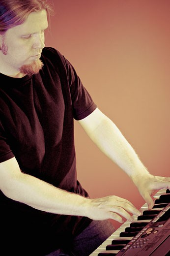 Mid adult man playing a piano : Stock Photo