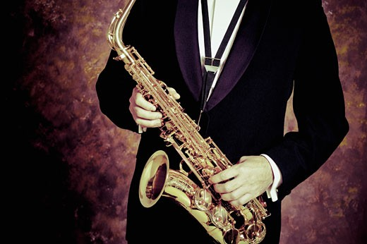 Mid section view of a person playing a saxophone : Stock Photo