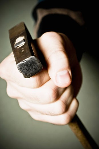 Close-up of a person's hand holding a hammer : Stock Photo