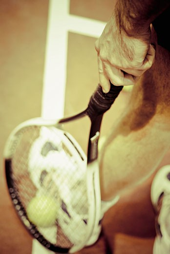 Low section view of a tennis player with a tennis racket and a tennis ball : Stock Photo