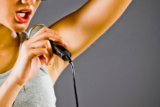 Stock Photo: 1758R-8767 Woman singing into a microphone