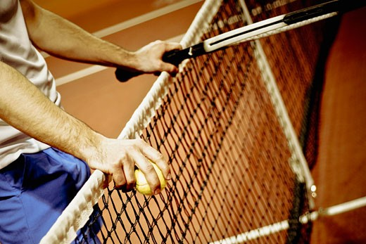 Mid section view of a person holding a tennis racket and tennis balls : Stock Photo