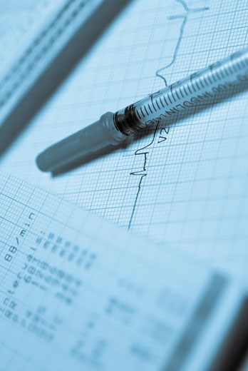 Close-up of a syringe on an ECG report : Stock Photo