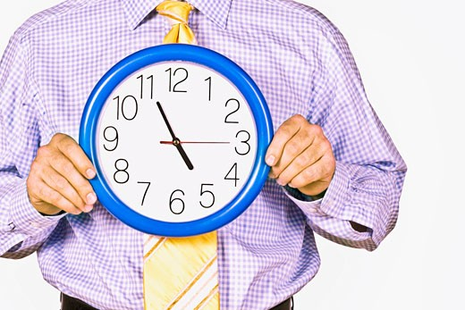 Close-up of a businessman holding a wall clock : Stock Photo