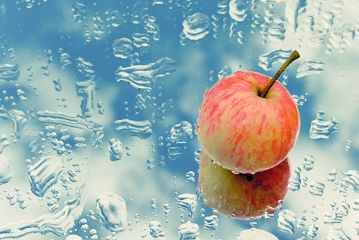 Close-up of an apple on a wet glass : Stock Photo