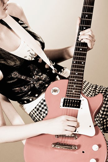 Stock Photo: 1758R-8992 Woman playing a guitar