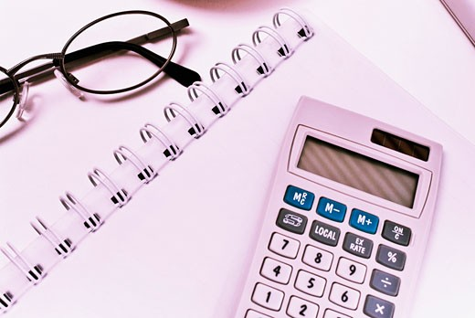 Close-up of a calculator and eyeglasses on a spiral notebook : Stock Photo