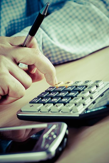 Close-up of a man's hand using a calculator : Stock Photo