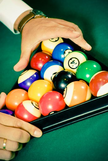 Stock Photo: 1758R-9035 Close-up of a person's hands racking up pool balls on a pool table