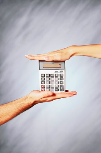 Stock Photo: 1758R-9038 Close-up of a man and a woman's hands holding a calculator