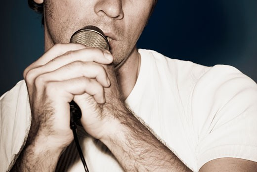 Man singing into a microphone : Stock Photo