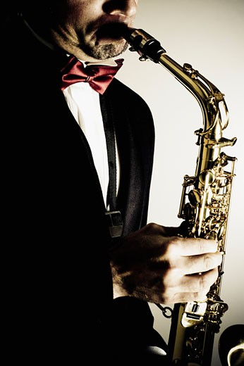 Close-up of a musician playing a saxophone : Stock Photo