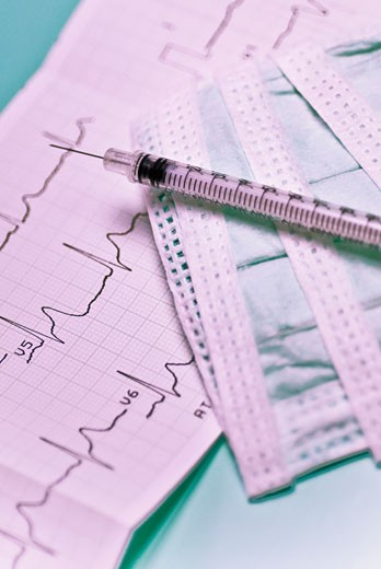 Close-up of an electro cardiogram report with a syringe : Stock Photo