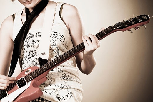 Woman playing a guitar : Stock Photo