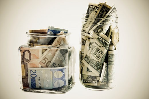 Close-up of two jars with Euros and dollar bills : Stock Photo