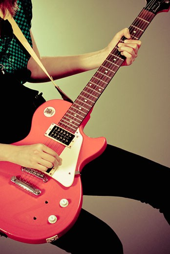 Stock Photo: 1758R-9294 Mid section view of a guitarist playing a guitar