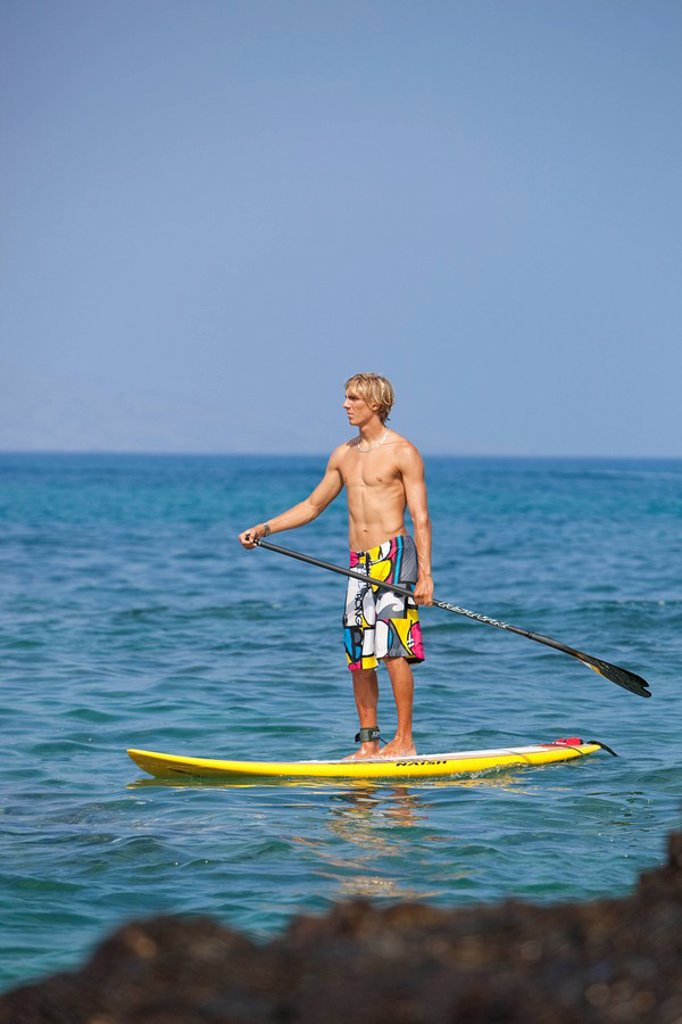 Hawaii, Maui, Makena, Athletic stand up paddle surfer in ocean : Stock Photo