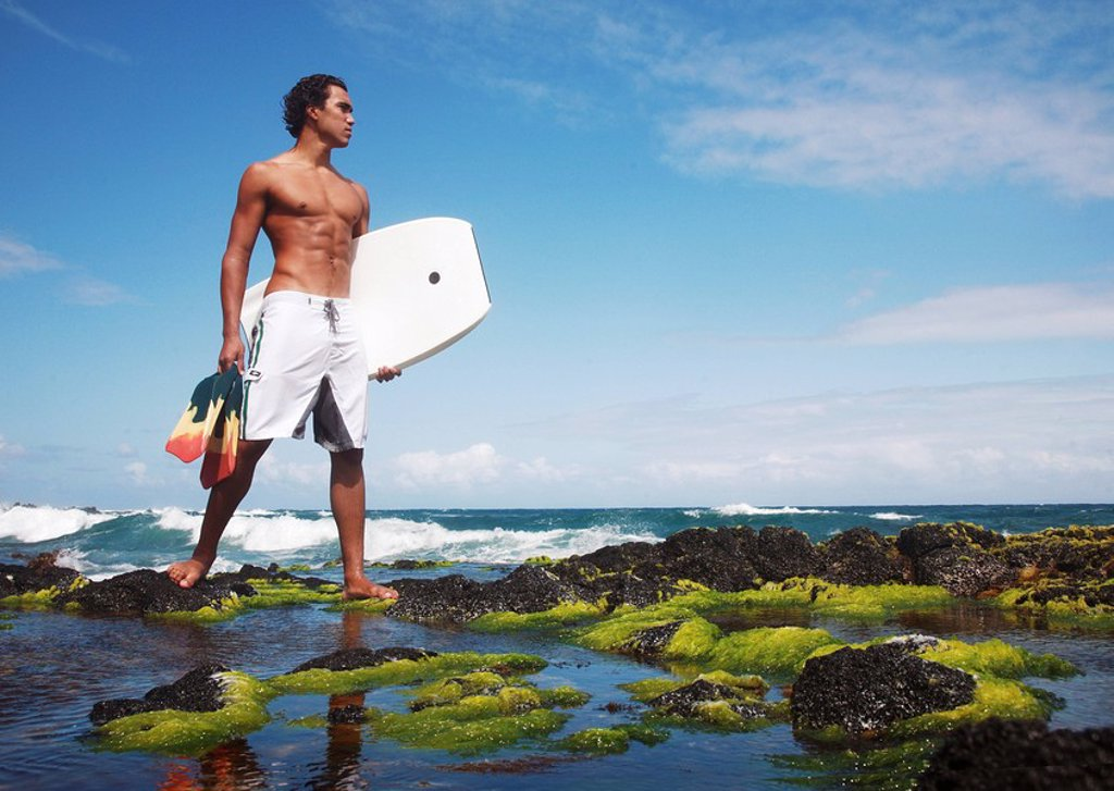 Hawaii, Oahu, Local bodyboarder standing on tidepool of rocks near the shoreline. : Stock Photo
