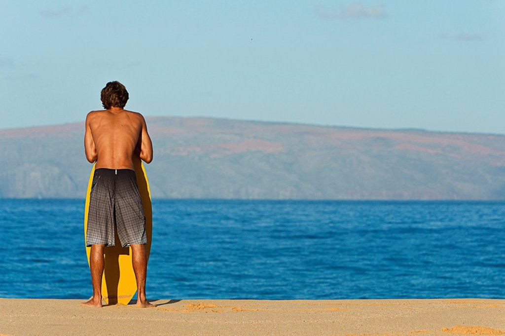 Hawaii, Maui, Makena, Skimboarder at on the beach looking out at ocean : Stock Photo