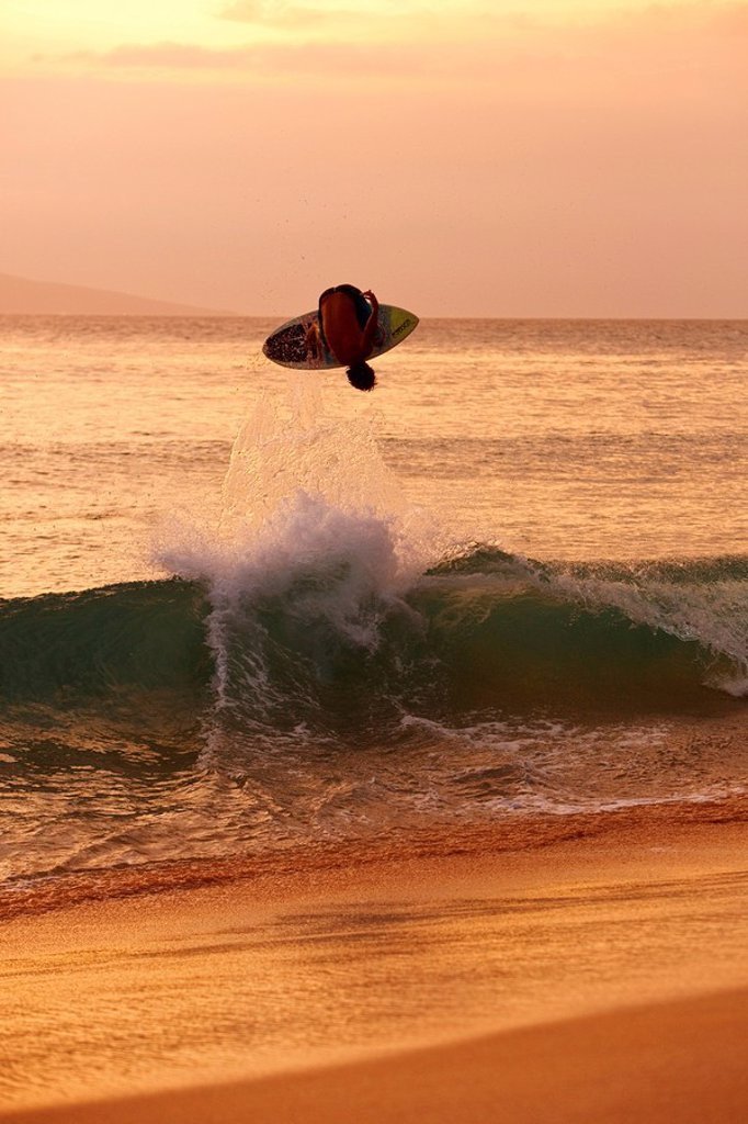 Hawaii, Maui, Makena, Skimboarder gets big air off a wave at sunset : Stock Photo
