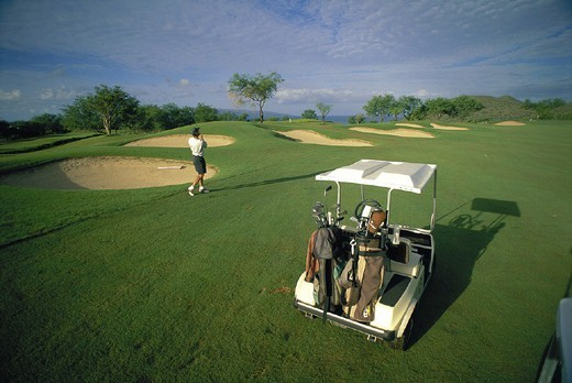 Hawaii Maui Makena golf cart on course, man in swing near sandtraps D1338 : Stock Photo