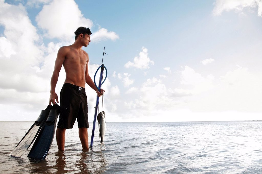 Stock Photo: 1760-13078 Hawaii, Oahu, Man holding his speargun, fins, and fish caught on a string standing in the water.