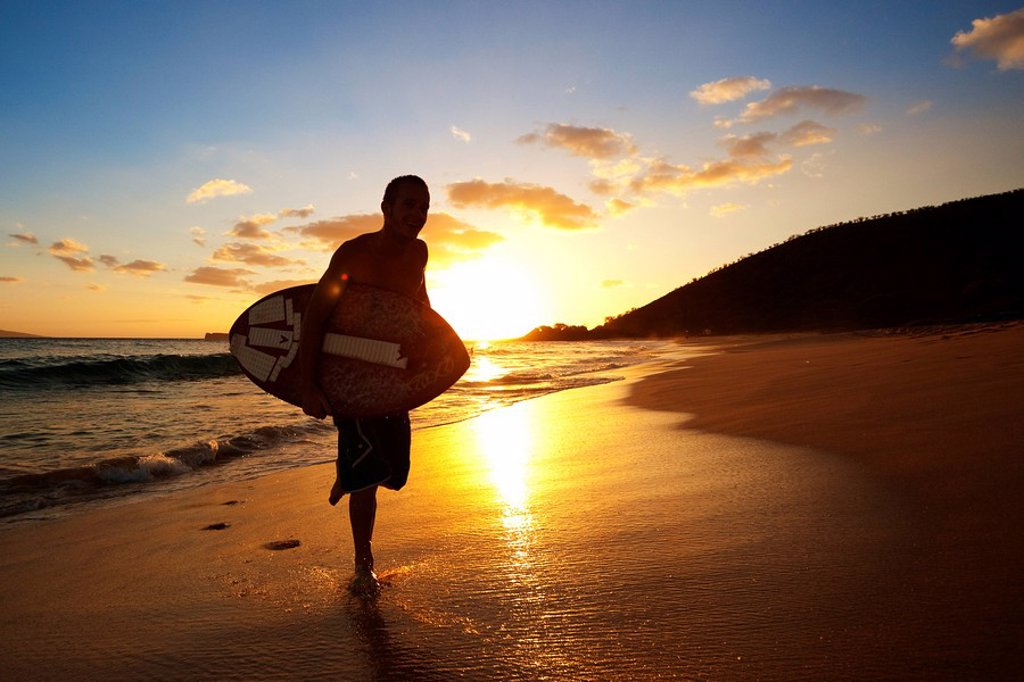 Hawaii, Maui, Makena, Skimboarder running up the beach : Stock Photo
