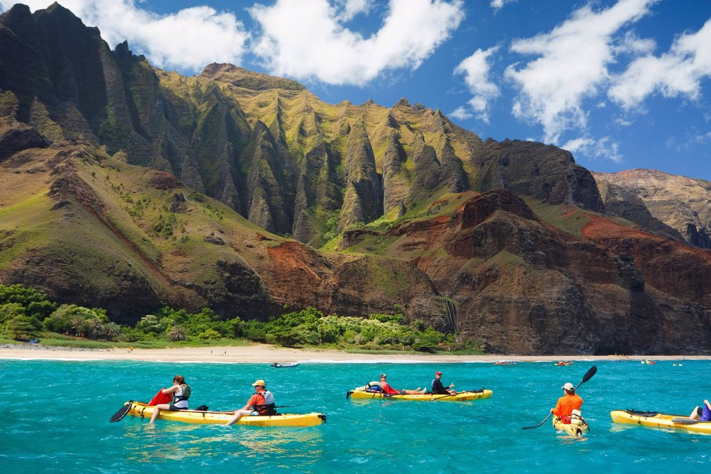 Hawaii, Kauai, Na Pali Coast, Group of kayakers paddling along coastline, Beautiful mountain ridges in background. Editorial Use Only. : Stock Photo