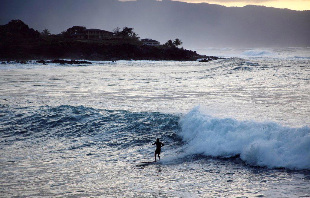 Hawaii, Oahu, North Shore, Waimea Bay, Surfer rides a wave back to shore. : Stock Photo