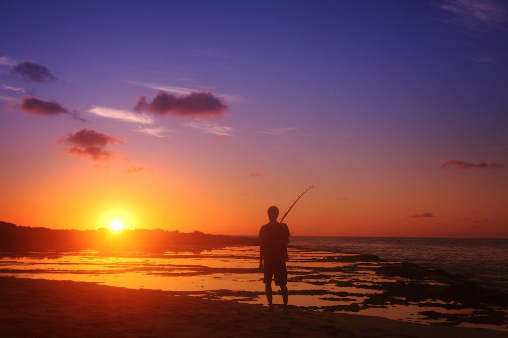 Hawaii, Silhouetted fisherman and sunset. : Stock Photo