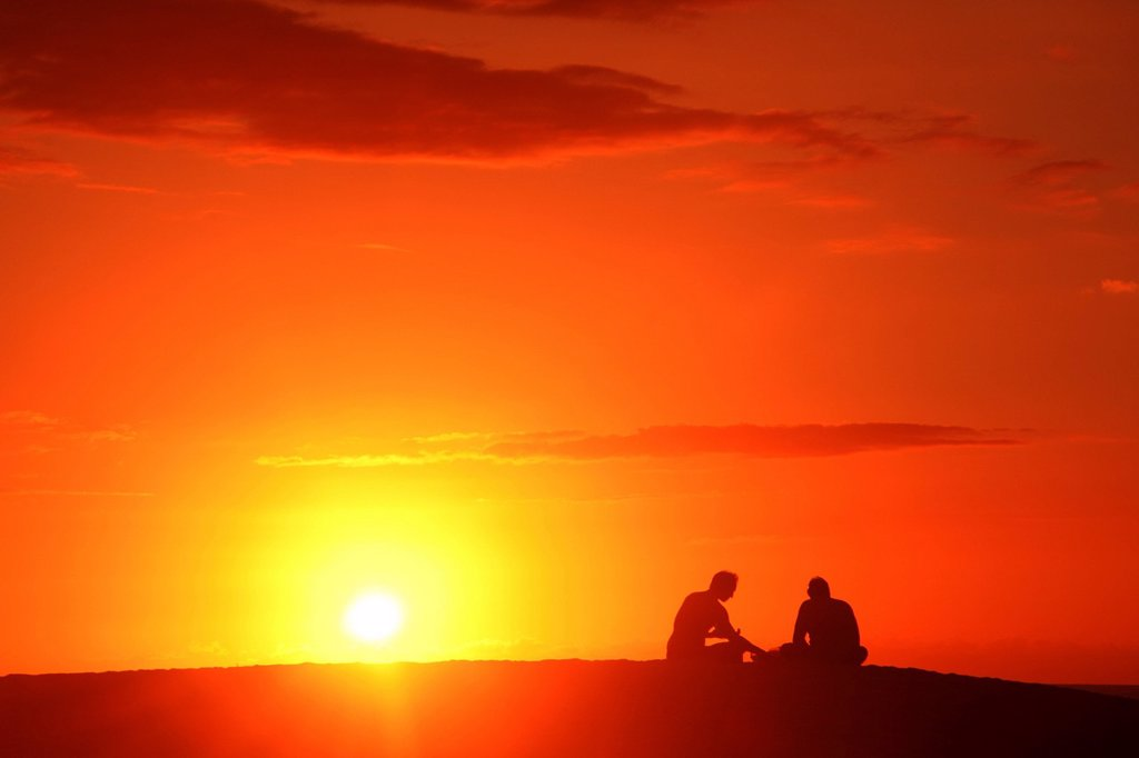 Hawaii, Oahu, Two silhouetted men enjoying the sunset. : Stock Photo
